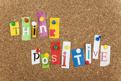 THINK POSITIVE. Single letters pinned on cork bulletin board stock image