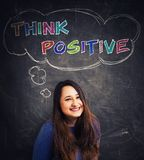 Think positive slogan. Cute young woman natural smile looking to camera over blackboard background and a thought bubble with the text think positive. Colorful stock image