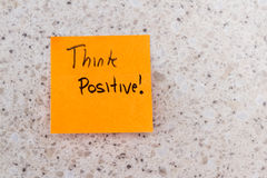 Think positive. Sticky note with a think positive message written on it on an office desk stock photography