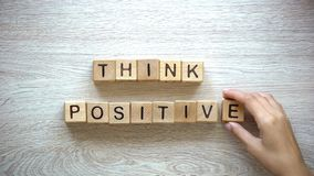 Think positive, woman making phrase of wooden cubes, motivation and inspiration. Stock photo stock photos