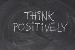 Think positively slogan on blackboard. Think positively slogan handwritten with white chalk on blackboard with strong eraser smudges Royalty Free Stock Photography