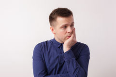 Think about problems. Young man is sad to think about something, rubs his chin Stock Photo
