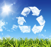 Think recycling. Cloud-shaped icon recycling in the sky on grass Stock Photos