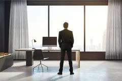 Think and research concept. Back view of young businessman looking out of window in modern interior with city view. Think and research concept. 3D Rendering Royalty Free Stock Images