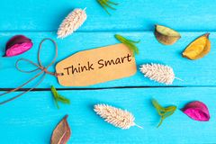 Think smart text on paper tag. With rope and color dried flowers around on blue wooden background royalty free stock photo