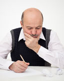 Think of the solution to the problem or a difficult task. Elderly man writes, draws something on a piece of paper, to fill in an application or a will Royalty Free Stock Photography