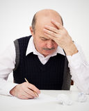 Think of the solution to the problem or a difficult task. Elderly man writes, draws something on a piece of paper, to fill in an application or a will Royalty Free Stock Photos