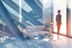 Think and success concept. Thoughtful young businessman looking out of window in modern interior wtih abstract city view. Double exposure royalty free stock photography