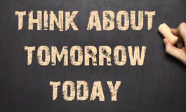 Think about tomorrow today ! - Female hand writing text on black Royalty Free Stock Image