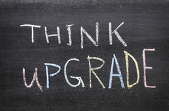 Think upgrade. Phrase handwritten on the school blackboard stock photography