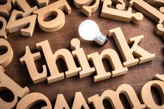 Think Wood Word. THINK word in scattered wood letters on the table with glowing light bulb royalty free stock images