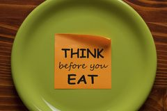 Think Before You Eat. Written on sticky note on the green plate. Health Tip royalty free stock image