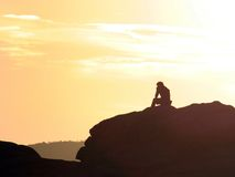 Thinker. A man sitting on a rock at a cliff edge and thinking during sunset Royalty Free Stock Photos