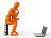 The Thinker. Look at more images with orange mannequinn and laptop in my portfolio Royalty Free Stock Image