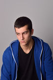 Thinker attractive young man in blue hoodie Stock Photos