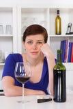 喝一杯红葡萄酒的年轻哀伤的thinkful妇女 免版税库存照片