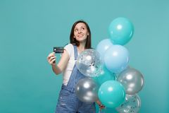 Thinkful young girl in denim clothes looking up holding credit bank card, celebrating with colorful air balloons