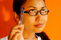 Thinking. Woman with glasses holding a pen thinking of something royalty free stock image