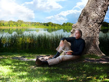 Thinking. A casually dressed man leans on a large tree trunk thinking about what to write in his journal. In the background is a calm lake Royalty Free Stock Photos