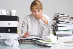 Thinking!!!. Businesswoman is sitting at a table full of paperwork stock photos