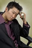 Thinking. A male business man thinking with his watch to his head Royalty Free Stock Image