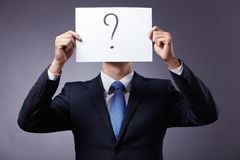 Thinking. Businessman in suit holding a sign with a question mark stock image