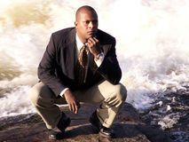 Thinking 2. Business man in a suit squatting down thinking in front of a rushing river royalty free stock images