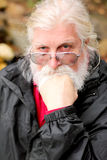 Thinking. A thinking aged man with long white hair, glasses and a full beard. Shallow depth of field Stock Images