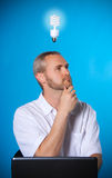 Thinking. Man with a beard with a light bulb on the laptop royalty free stock image