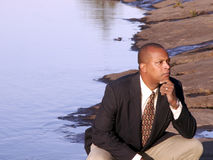 Thinking. Business man in a suit squatting down thinking royalty free stock image