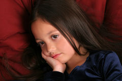 Thinking about it. Studio portrait of a young girl with long, dark hair with a blue dress on against a burgandy background Stock Photos