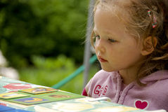 Thinking. Little girl is thinking about the right card to play Royalty Free Stock Images
