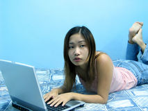 Thinking. An asian girl thinking while in front of her notebook royalty free stock image