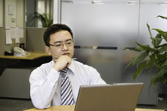 Thinking. Asian business executive doing some thinking in office Stock Photo
