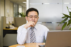 Thinking. Asian business executive doing some thinking in office Royalty Free Stock Photos