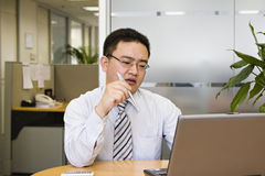 Thinking. Asian business executive doing some thinking in office Royalty Free Stock Image