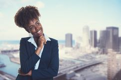 Thinking african american businesswoman with skyline of city. In the background stock photos