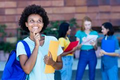 Thinking african american female student with group of students. Outdoor in summer at university stock photo