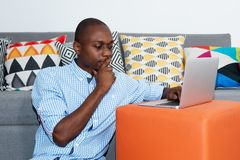 Thinking african american man with laptop. At home stock photos