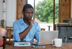 Thinking african american man with laptop Royalty Free Stock Photography