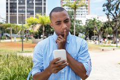 Thinking african american man with mobile phone. Outdoor in the summer in the city royalty free stock images