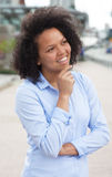 Thinking african american woman in the city. With modern buildings in the background stock images