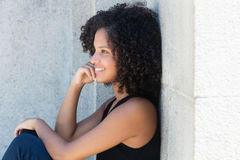 Thinking african american woman with curly black hair. Outdoor in the summer Royalty Free Stock Photo
