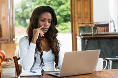 Thinking african american woman with long hair at computer. R at desk at home royalty free stock photo