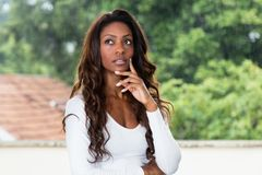 Thinking african american woman with long hair. Outdoors in the summer Stock Images
