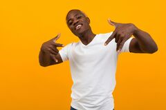 Thinking African Black Man In A White T-shirt With A Layout Posing On A Yellow Background Royalty Free Stock Photos