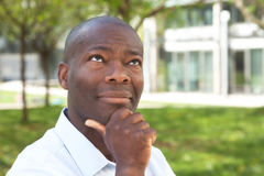 Thinking african man outside. In a park with trees, meadow and building in the background royalty free stock image