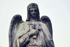 Thinking angel with cross statue, Malostransky cemetery, Prague, Czech Republic. Intended angel with cross in hand statue, Malostransky cemetery, Prague, Czech Stock Image
