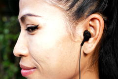 Thinking asian lady with headphones Stock Photos