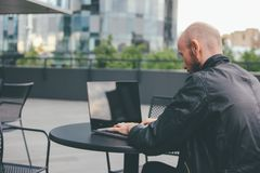 Thinking attractive adult successful bald bearded man in black jacket with laptop in street cafe at city stock photography